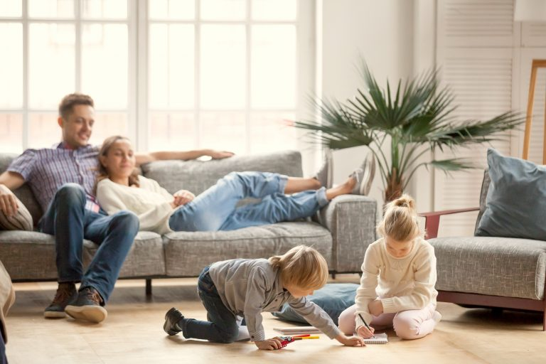 Children Sister And Brother Playing Drawing Together On Floor While Young Parents Relaxing At Home O