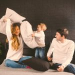 Family Having Funny Pillow Fight On Bed. Parents Spending Free Time With Their Son. Young Family Bei