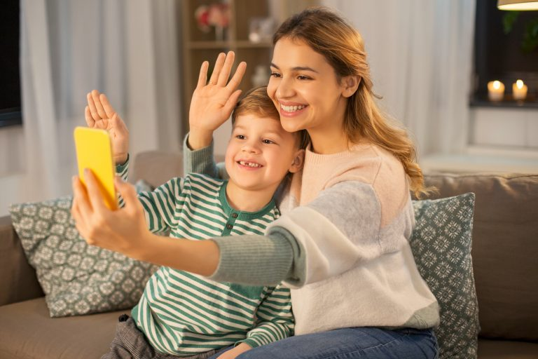 family, technology and people concept - happy smiling mother and little son with smartphone having v