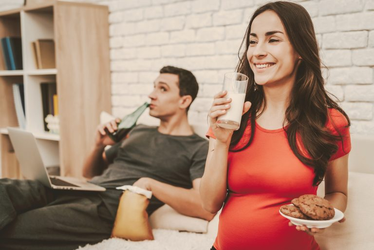 Couple Is Sitting On Couch. Woman Is Drinking A Milk And Eating A Cookie. Woman Is Pregnant And Smil