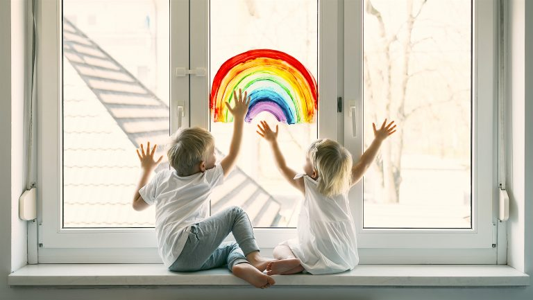 Little Children On Background Of Painting Rainbow On Window. Photo Of Kids Leisure At Home. Positive