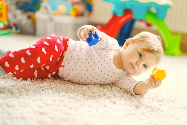 Little Cute Baby Girl Learning To Crawl. Healthy Child Crawling In Kids Room With Colorful Toys. Bac